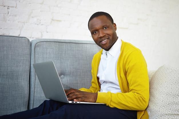 Красивый темнокожий блоггер в желтом кардигане за клавиатурой на обычном портативном компьютере публикует новый пост в своем онлайн-блоге, вдохновляет на выражение, смотрит и улыбается Бесплатные Фотографии