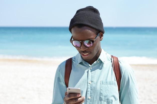 おしゃれな服を着たハンサムな浅黒い肌の学生。海辺での大学卒業後、自由な時間を過ごし、ビーチ沿いを散歩し、オンラインで友達にメッセージを送っています。人、ライフスタイル、現代のテクノロジー 無料写真
