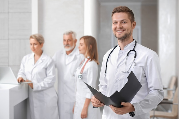 Handsome doctor posing, group of therapists standing behind. Premium Photo