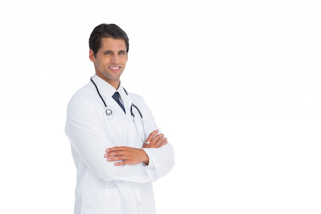 Handsome doctor smiling with arms crossed Premium Photo