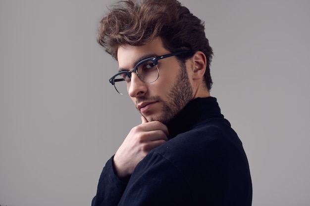Handsome elegant man with curly hair wearing black turtleneck and glasses Premium Photo