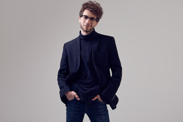 Handsome elegant man with curly hair wearing suit and glasses Premium Photo