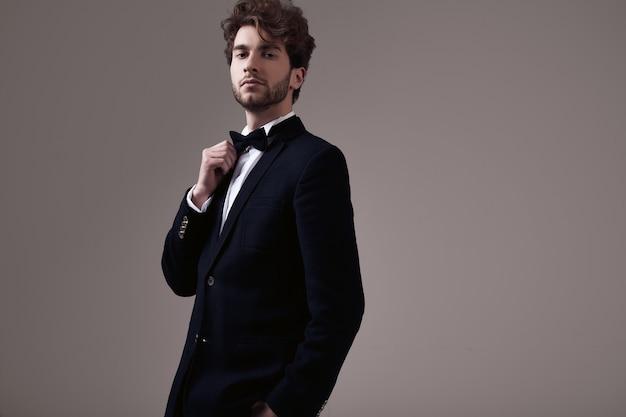 Handsome elegant man with curly hair wearing tuxedo Premium Photo