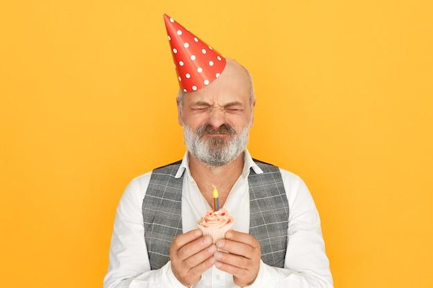 Красивый элегантный старший мужчина с густой седой бородой в шляпе-конусе закрывает глаза, загадывая желание Бесплатные Фотографии