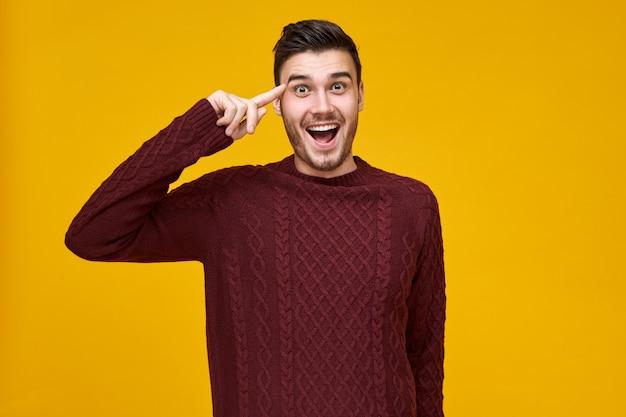 Bel giovane maschio emotivo che esprime sei un'emozione pazza, tenendo il dito indice vicino alla testa. ragazzo eccitato in maglione lavorato a maglia rotolando il dito alla tempia, aprendo ampiamente la bocca. pensa prima di agire Foto Gratuite