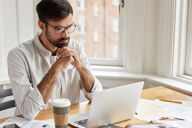 Il bel dipendente ha uno sguardo serio e concentrato al computer portatile, indossa occhiali trasparenti e camicia bianca, lavora con il computer portatile, Foto Gratuite
