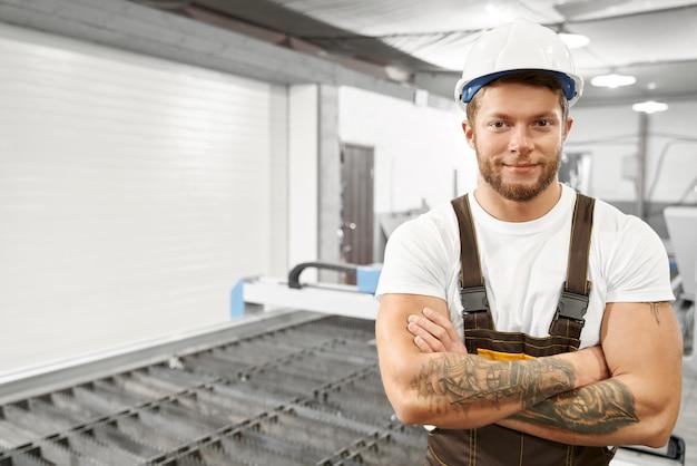 Ingegnere bello che posa sulla fabbrica vicino alla taglierina del plasma. Foto Gratuite