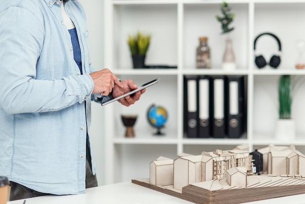 잘 생긴 엔지니어가 건설 프로젝트에 참여하고 미래 건물의 모형을 검토하고 태블릿 Pc에서 메모를 작성합니다. 프리미엄 사진