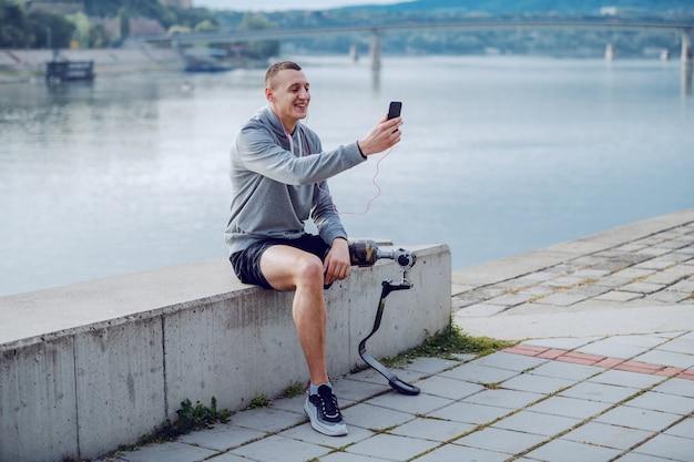 ハンサムなフィットスポーティな白人の障害者スポーツウェアで、岸壁に座っているとスマートフォンでメッセージを入力して義足。 Premium写真