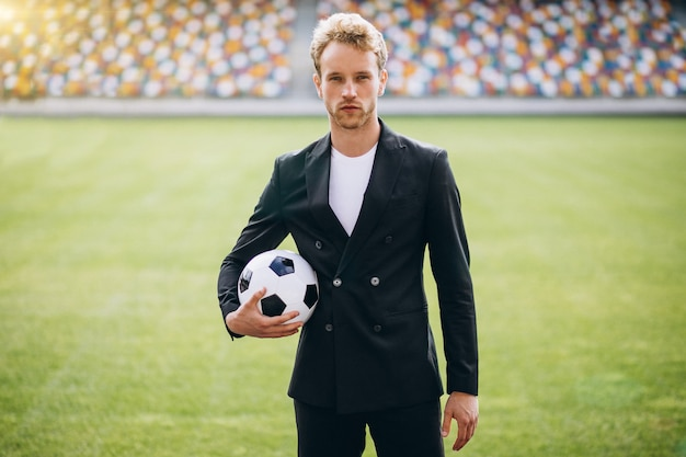 Handsome football player at stadium in business suit Free Photo
