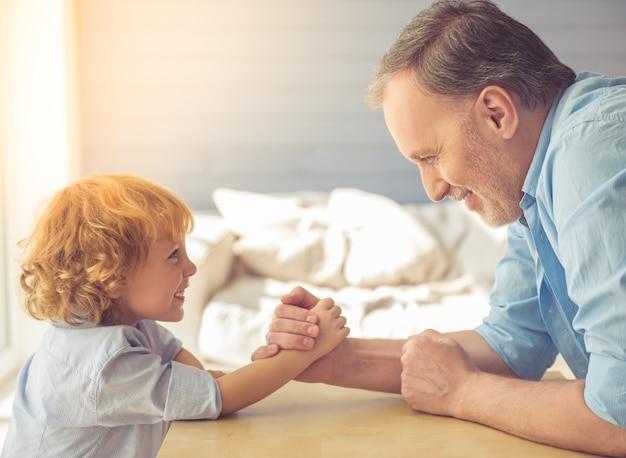 Handsome grandpa and grandson are wrestling and smiling. Premium Photo