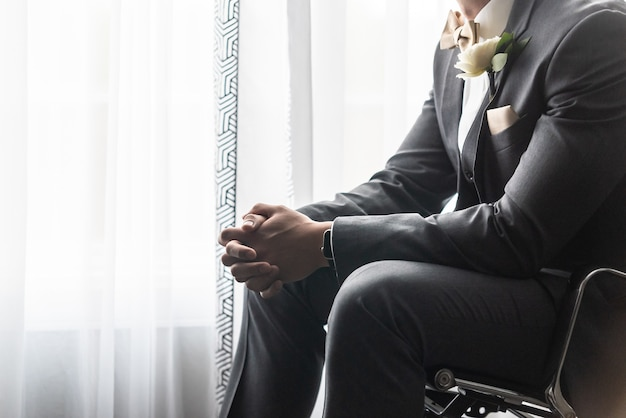 Handsome groom in a black suit praying before the wedding ceremony Free Photo