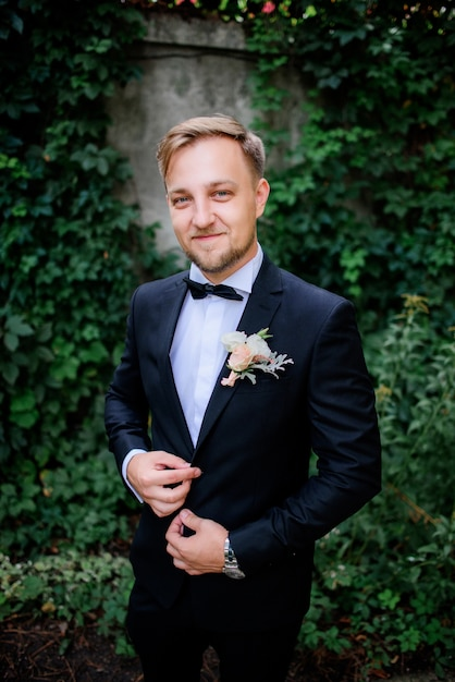 Handsome groom in black suit and white rose boutonniere stands in the garden Free Photo