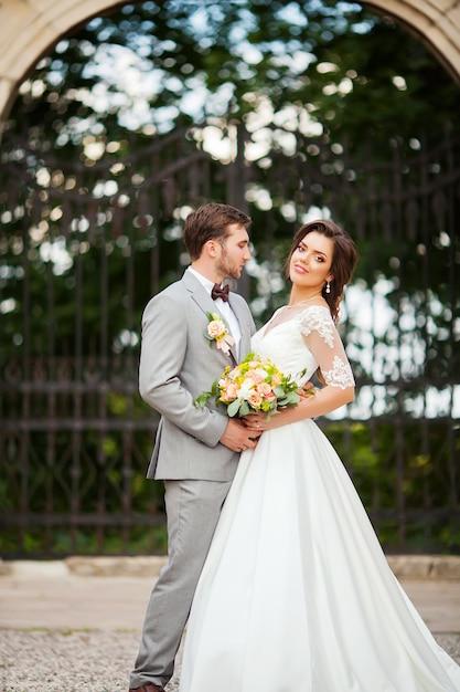 Handsome groom hugging beautiful bride with bouquet in romantic european park Premium Photo