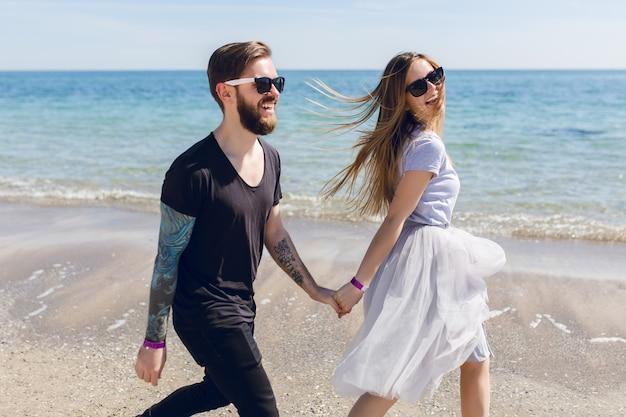 Bel ragazzo in occhiali da sole neri con la barba cammina sulla spiaggia vicino al mare che tiene una mano di bella donna con i capelli lunghi Foto Gratuite
