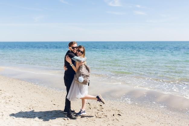 Bel ragazzo in maglietta nera e pantaloni sta abbracciando bella donna con i capelli lunghi vicino al mare Foto Gratuite