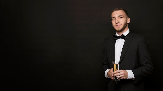 Handsome guy in dinner jacket with glass of drink Free Photo