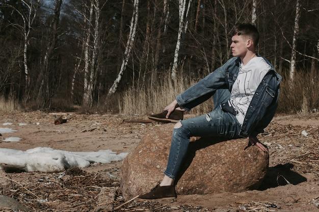 Красивый парень сидит на камне возле лесной полосы весной и смотрит на горизонт. Premium Фотографии
