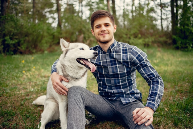 Handsome guy in a summer park with a dog Free Photo