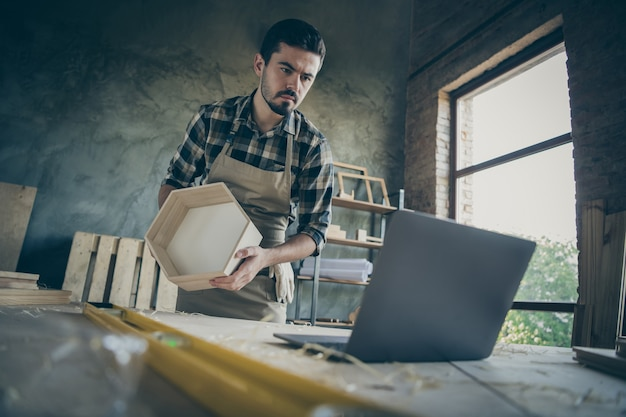 Handsome guy watch notebook online lesson how to make old shelf renovation modern design handmade wooden industry sawdust table garage workshop indoors Premium Photo