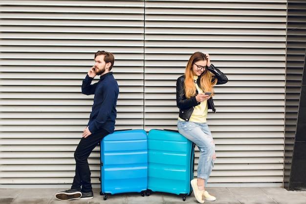 Bel ragazzo con la barba appoggiato sulla valigia su sfondo grigio a strisce e parlando al telefono. bella ragazza con i capelli lunghi in bicchieri vicino appoggiato anche sulla valigia e sta scrivendo sul telefono. Foto Gratuite