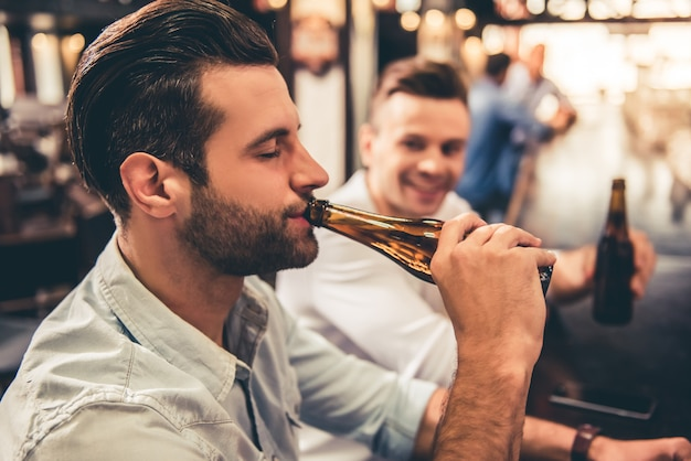 Handsome guys are drinking beer in bar. Premium Photo