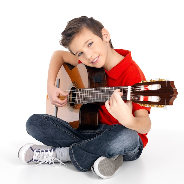 어쿠스틱 기타에서 재생되는 잘 생긴 행복 한 소년 무료 사진