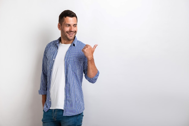 Handsome happy man pointing by his big finger sideways. Premium Photo