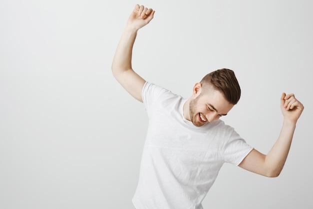 Красивый счастливый молодой человек танцует в белой футболке над серой стеной Бесплатные Фотографии
