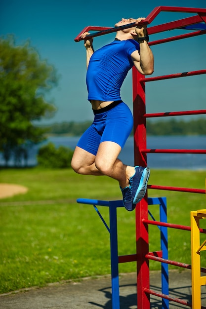 Handsome healthy happy srtong athlete male man exercising at the city park - fitness concepts on a beautiful summer day on horizontal bar Free Photo
