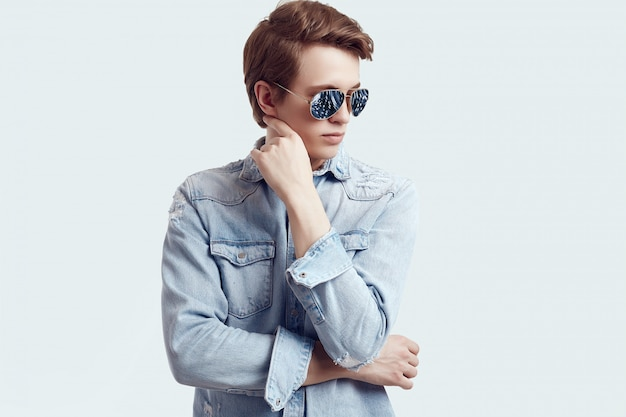 Handsome hipster man in fashion sunglasses wearing jeans jacket Premium Photo