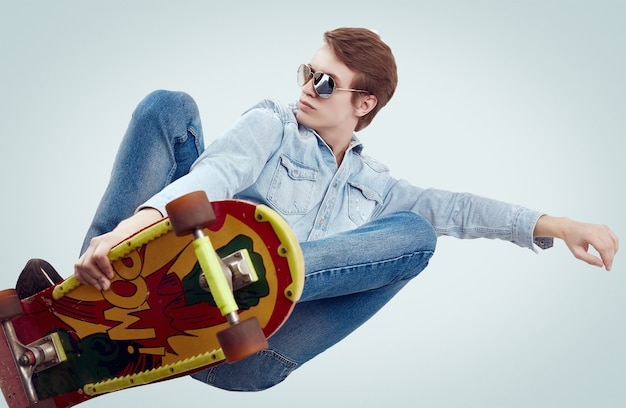 Handsome hipster man in jeans jacket doing the flip on stylish skateboard Premium Photo