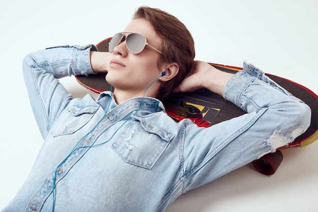 Handsome hipster man in jeans jacket and sunglasses lies on a skateboard Premium Photo
