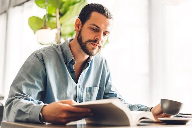 Красивый хипстерский мужчина расслабляется, читая бумажную книгу и глядя на страницу журнала, сидя на стуле в кафе и ресторане Premium Фотографии