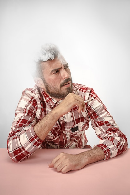 Handsome hipster man smoking cigarette at home. man looking upwards and enjoying spending free time. Free Photo