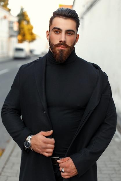 거리에서 가을 날에 검은 유행 코트에 수염을 가진 잘 생긴 힙 스터 남자 프리미엄 사진