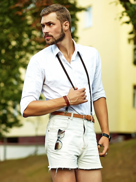 Handsome hipster model man in stylish summer clothes posing Free Photo