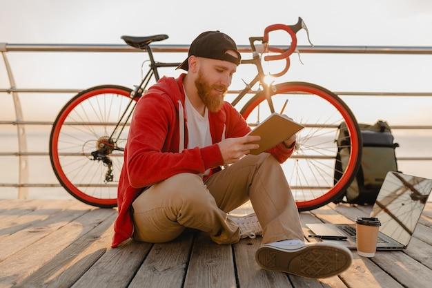 Красивый бородатый мужчина в стиле хипстера изучает онлайн-фрилансер, пишущий, делая заметки с рюкзаком и велосипедом в утреннем восходе солнца у моря, здоровый активный образ жизни, путешественник с рюкзаком Бесплатные Фотографии