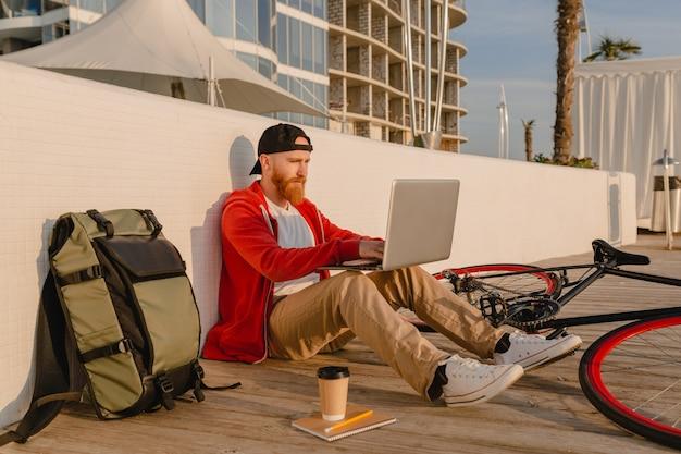 Красивый бородатый мужчина в стиле хипстера, работающий онлайн-фрилансером на ноутбуке с рюкзаком и велосипедом, активный путешественник с рюкзаком Бесплатные Фотографии