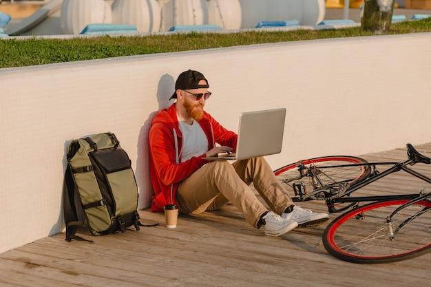 Красивый бородатый мужчина в стиле хипстера, работающий онлайн-фрилансером на ноутбуке с рюкзаком и велосипедом в утреннем восходе солнца у моря, здоровый активный образ жизни, путешественник с рюкзаком Бесплатные Фотографии
