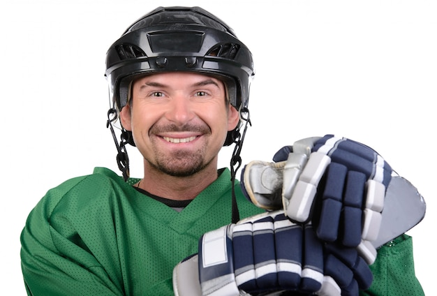 Handsome hockey player is smiling at camera. Premium Photo