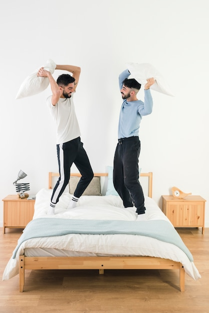 Handsome homosexual couple fighting with pillow on bed Free Photo