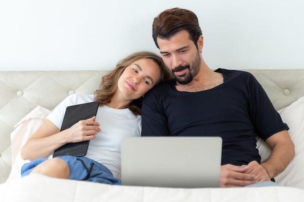 Красивый муж и красивая жена чувствуют себя романтической парой, смотрящей фильмы с портативного компьютера в спальне Бесплатные Фотографии
