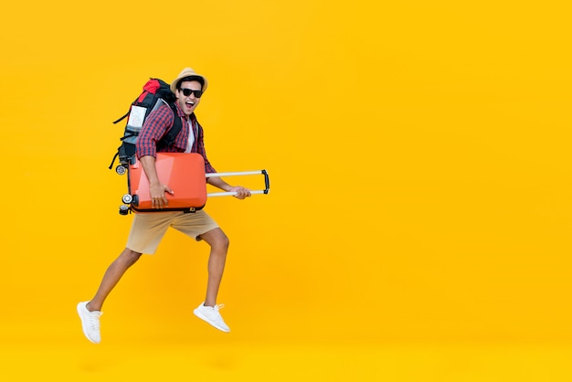 Handsome indian tourist man with backpack holding baggage and jumping Premium Photo