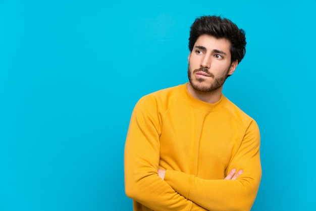 Handsome over isolated blue wall with confuse face expression Premium Photo
