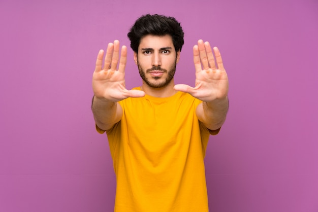 Handsome over isolated purple wall making stop gesture and disappointed Premium Photo