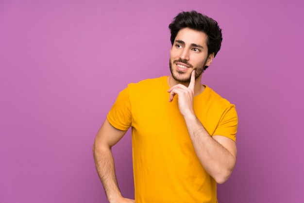 Handsome over isolated purple wall thinking an idea while looking up Premium Photo
