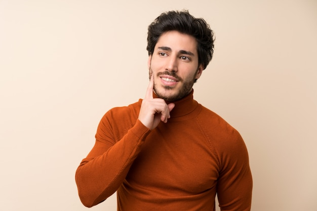 Handsome over isolated wall thinking an idea while looking up Premium Photo
