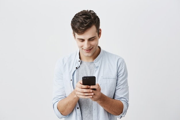 Handsome joyful student with dark hair wearing blue shirt messaging, typing message, using free onlipe app on his smartphone, looking at screen with smile, posing . Free Photo