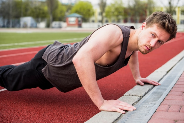 Handsome male athlete doing pushup on race track Free Photo